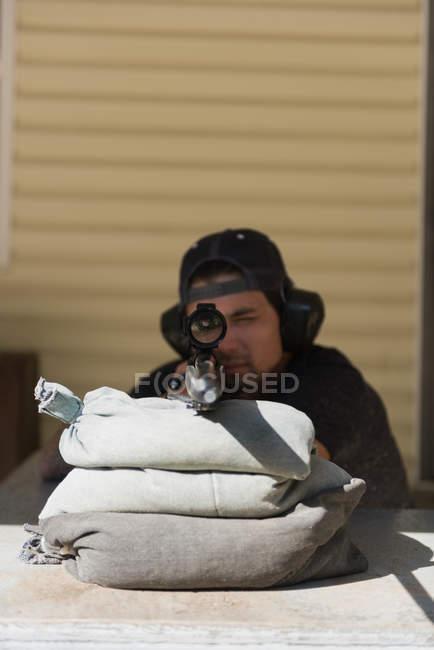Homem apontando o rifle sniper no alvo no tiro ao alvo em um dia ensolarado — Fotografia de Stock