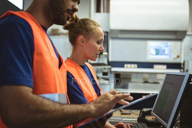 Zwei Arbeiter arbeiten in Fabrik am Computer — Stockfoto