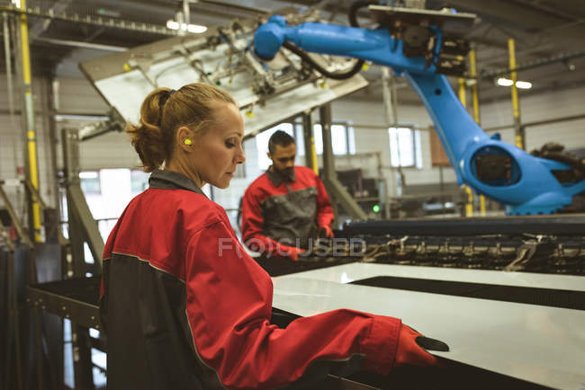Trabajadora comprobando una lámina de vidrio en fábrica - foto de stock