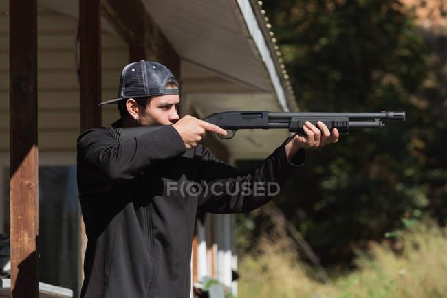 Mann zielt an sonnigem Tag mit Scharfschützengewehr auf Scheibe im Schießstand — Stockfoto