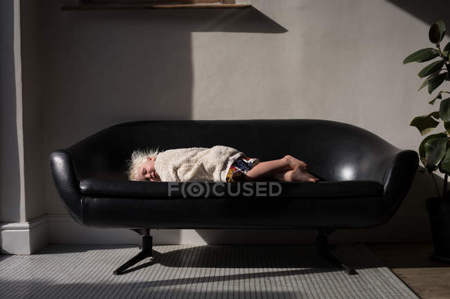 Toddler girl sleeping on sofa in living room at home. — one ...