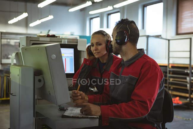 Zwei Arbeiter diskutieren miteinander in der Fabrik — Stockfoto