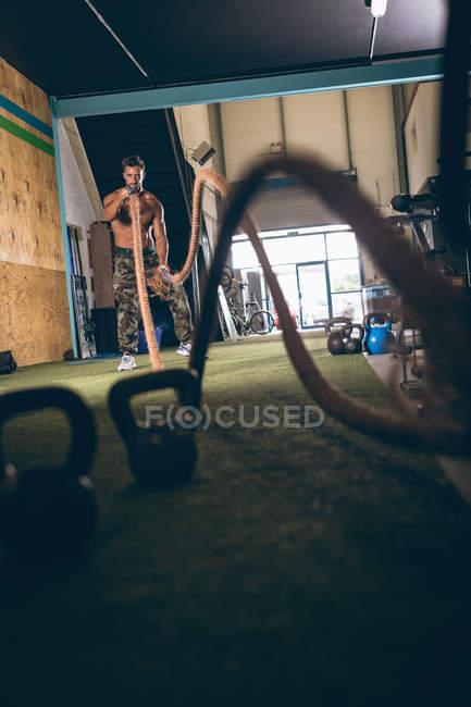 Решительный мускулистый мужчина тренируется с веревкой в фитнес-студии — стоковое фото