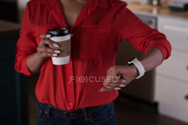 Mid section of female office executive checking time on smartwatch at creative office — Stock Photo