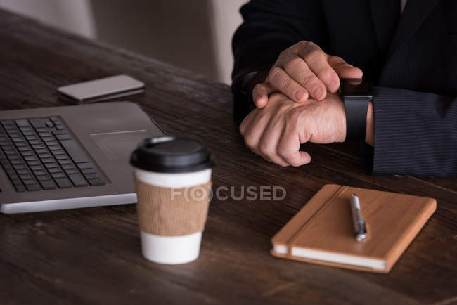 Mid section of businessman checking smart watch in creative office — Stock Photo