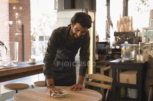 Smiling waiter cleaning the table in coffee shop — Stock Photo