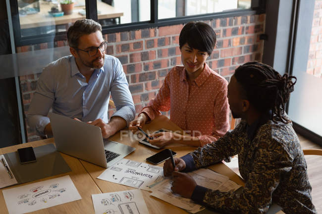 Executives discussing documents with laptop in meeting room at office. — Stock Photo
