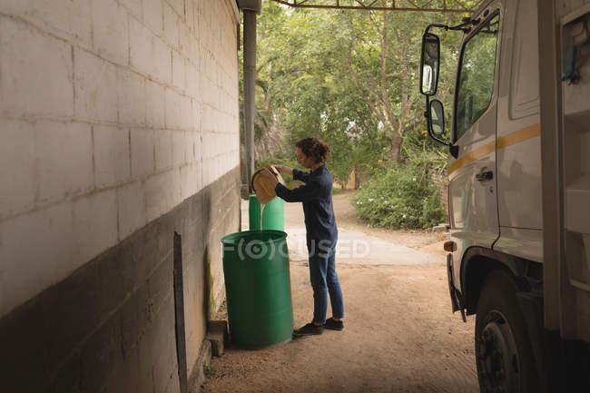 Mulher derramando água em barril de armazenamento na oficina — Fotografia de Stock