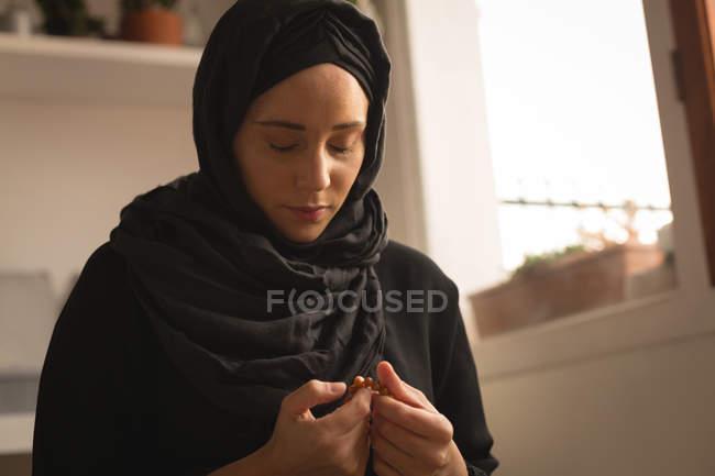 Muslimische Frau mit Gebetskette zu Hause beten — Stockfoto