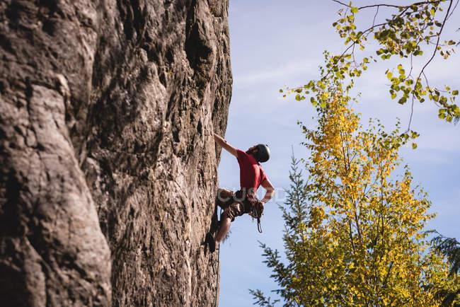 Escalador determinado escalando el acantilado rocoso - foto de stock
