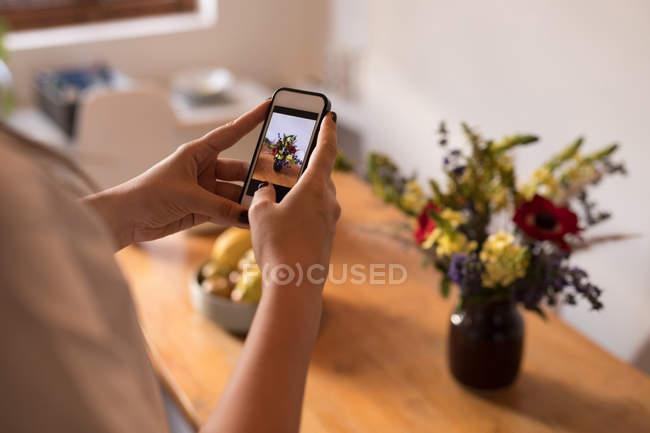 Seção média da mulher clicando imagem no telefone celular em casa — Fotografia de Stock