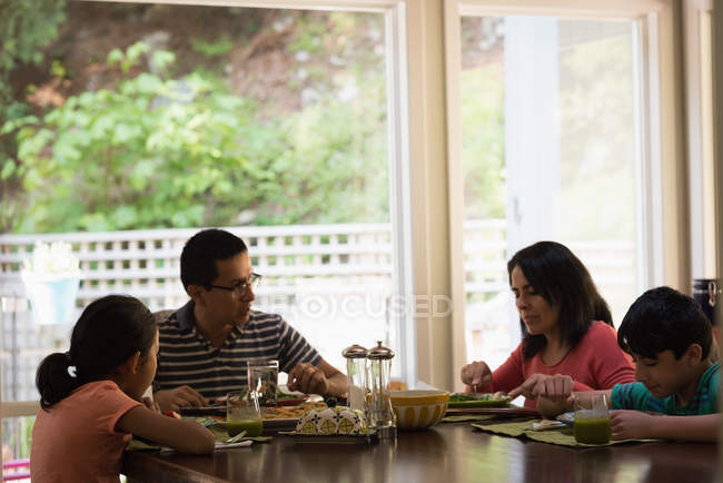 Family having breakfast on dinning table at home — Stock Photo