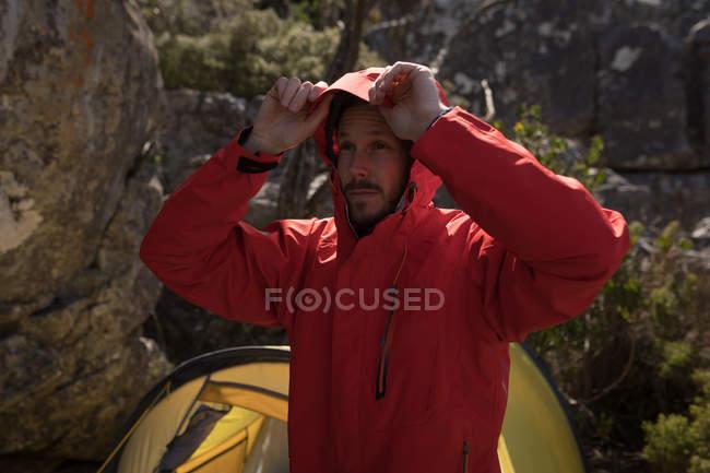 Randonneur debout près de la tente portant un bonnet de veste par une journée ensoleillée — Photo de stock