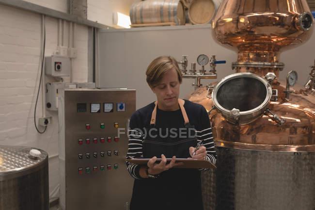 Trabajadora, escribir en el portapapeles en fábrica - foto de stock
