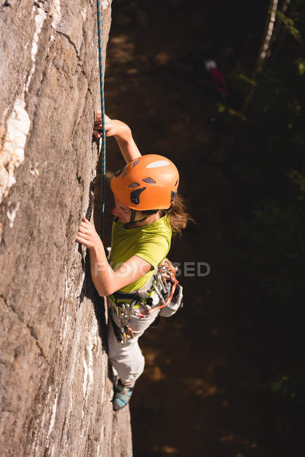 Determined female climber climbing the rocky mountain — Stock Photo