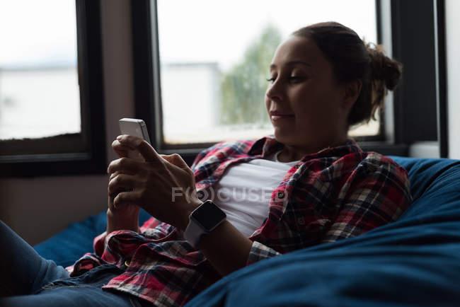 Женщина исполнительный расслабляющий на кресле и с помощью мобильного телефона в офисе — стоковое фото