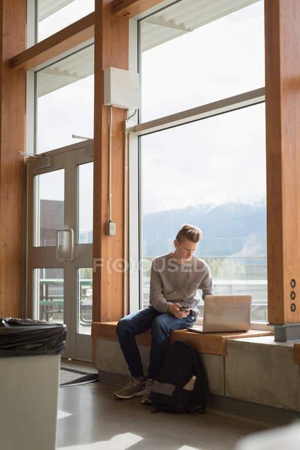 Підлітком, використовуючи ноутбук у університет — стокове фото