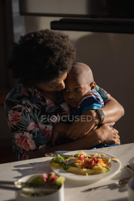 Mother embracing son at dinning table. — Stock Photo