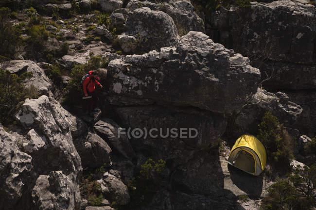 Randonneur descendant les rochers vers la tente par une journée ensoleillée — Photo de stock