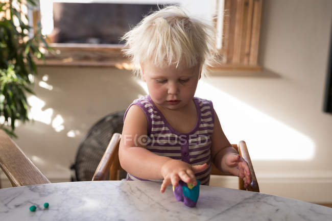 Toddler girl playing with clay at home. — Stock Photo