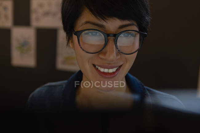 Close-up of female executive in glasses working by computer in office. — Stock Photo