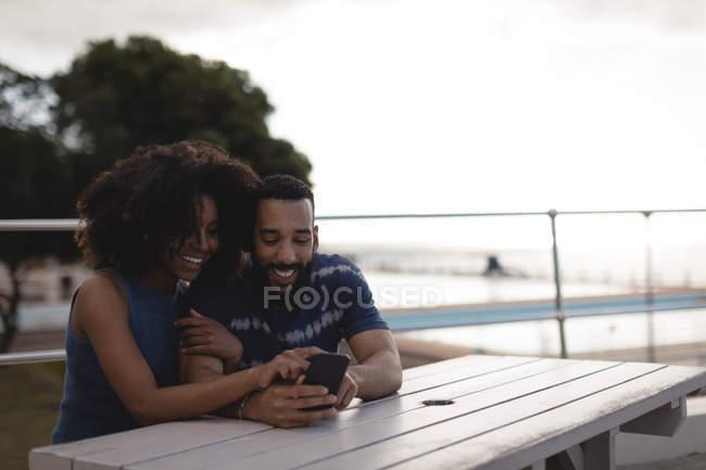 Paar mit Handy auf Promenade an sonnigen Tag — Stockfoto