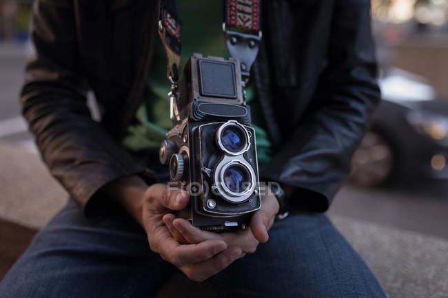 Seção média do fotógrafo com câmera sentada na parede circundante perto da rua — Fotografia de Stock