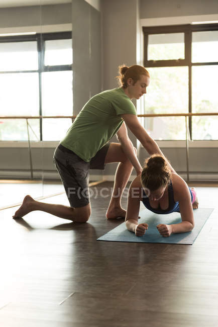 Trainer assisting woman in practicing yoga at fitness studio. — Stock Photo