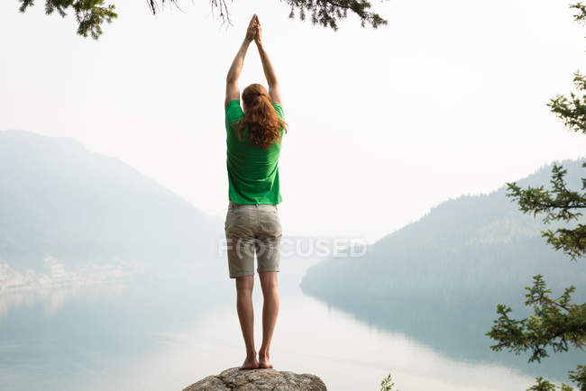 Подходящий человек, выполняющий упражнения на растяжку на краю скалы на рассвете — стоковое фото
