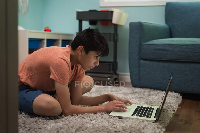 Attentive boy using laptop at home — Stock Photo