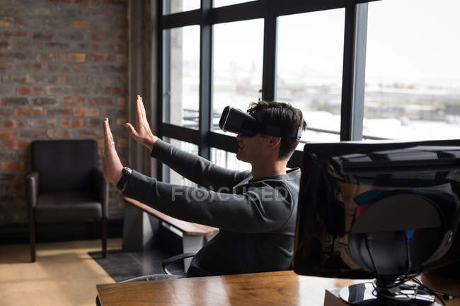 Male executive using virtual reality headset in office with arms outstretched. — Stock Photo