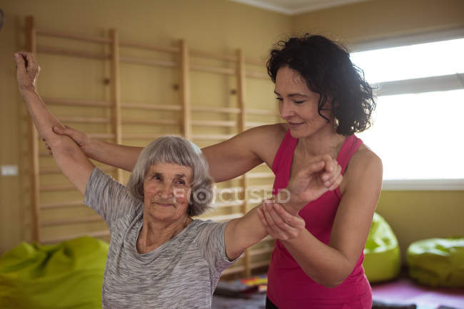 Female therapist assisting senior woman with hand exercise at nursing home — Stock Photo