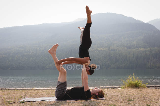 Side view of sporty women practicing acro yoga near the sea coast — Stock Photo
