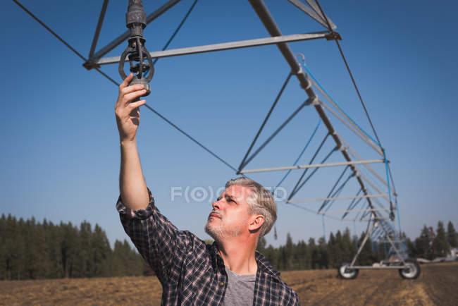 Fermier vérifiant le système d'irrigation dans le champ par une journée ensoleillée — Photo de stock