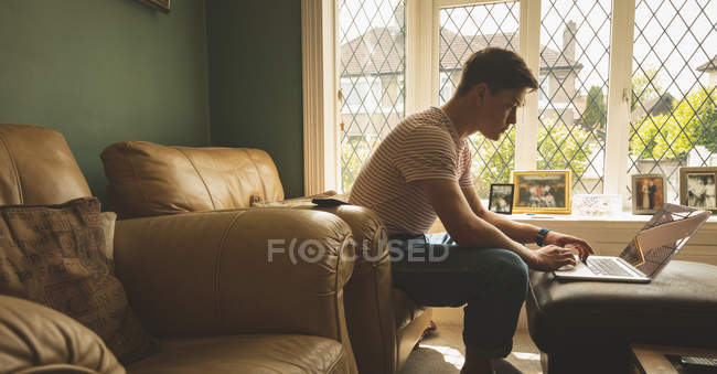 Человек использует ноутбук в гостиной дома, вид сбоку . — стоковое фото