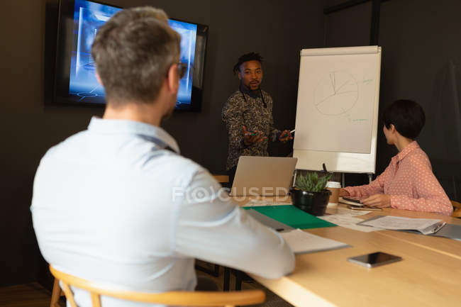 Business people discussing over whiteboard in meeting room at office. — Stock Photo