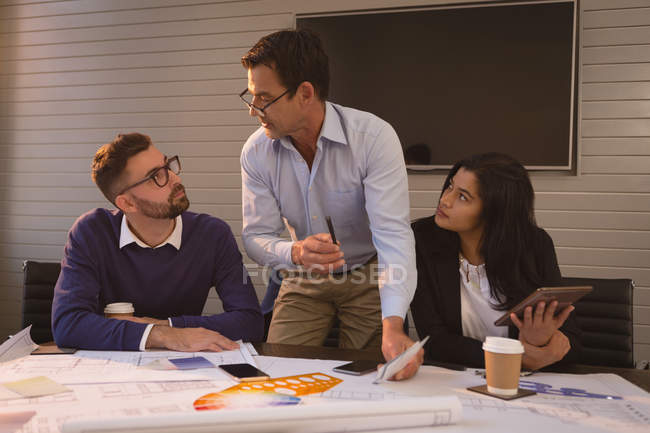Business people discussing blueprint and graph chart in office — Stock Photo