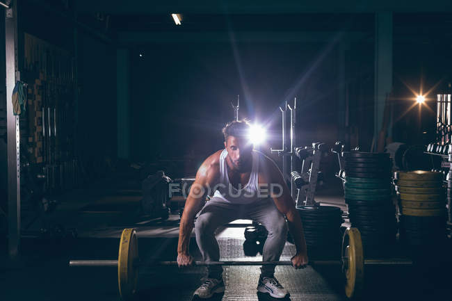 Portrait of muscular man exercising with barbell in the fitness studio — Stock Photo