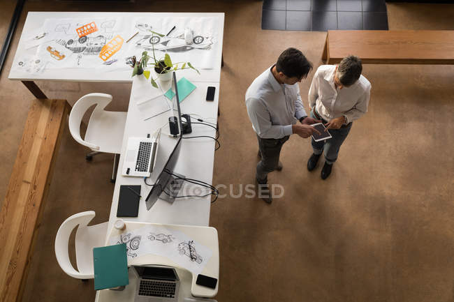 Business colleagues discussing over digital tablet in office. — Stock Photo