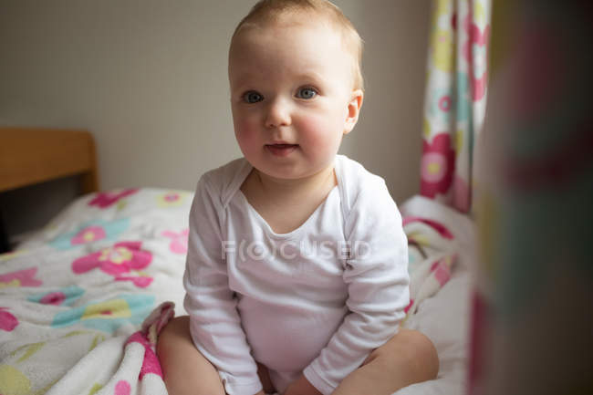 Baby girl sitting on bedroom at home — Stock Photo
