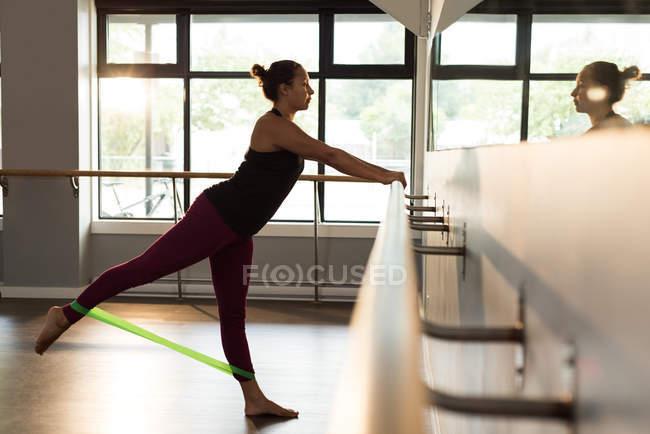 Женщина тренируется с группой сопротивления в фитнес-студии . — стоковое фото