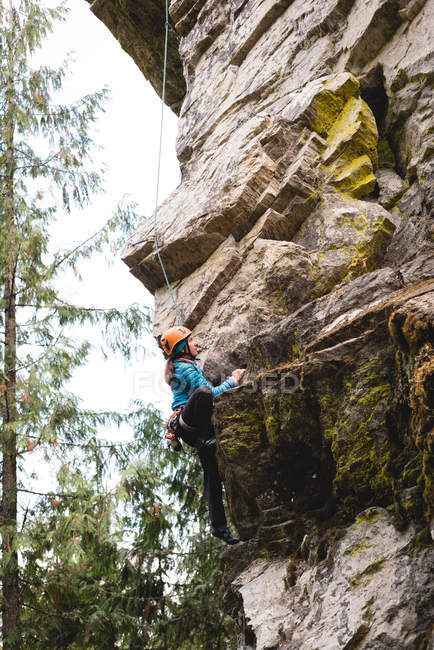 Determined female climber climbing the rocky cliff — Stock Photo