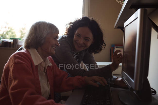 Caretaker assisting senior woman while working on computer at nursing room — Stock Photo