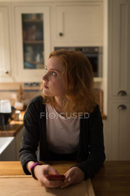 Frau schaut weg, während sie zu Hause ihr Handy in der Küche benutzt — Stockfoto