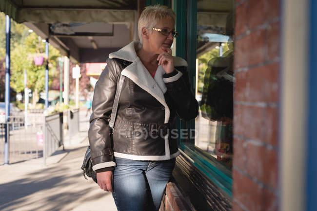 Старшая женщина заглядывает в стеклянное окно возле книжного магазина — стоковое фото