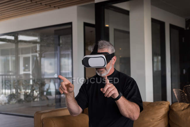 Male office executive experiencing virtual reality headset on sofa at creative office — Stock Photo