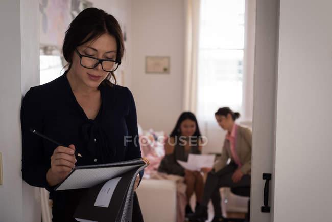 Smiling fashion designer sketching in design studio. — Stock Photo