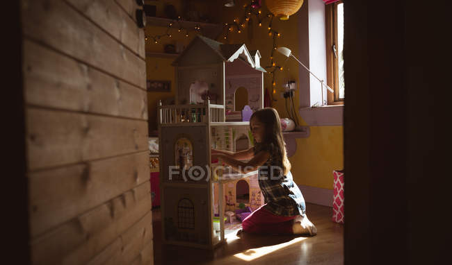 Girl playing with dollhouse in bedroom at home — Stock Photo