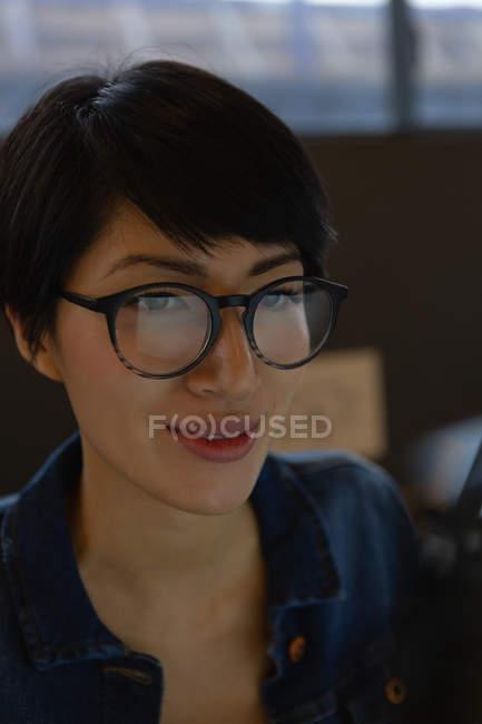 Primo piano dell'esecutivo femminile in occhiali lavorando da un computer in ufficio. — Foto stock