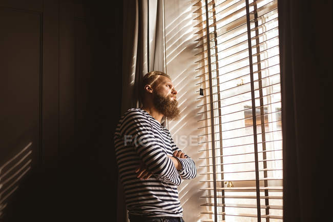 Thoughtful man watching out from the window at home — Stock Photo